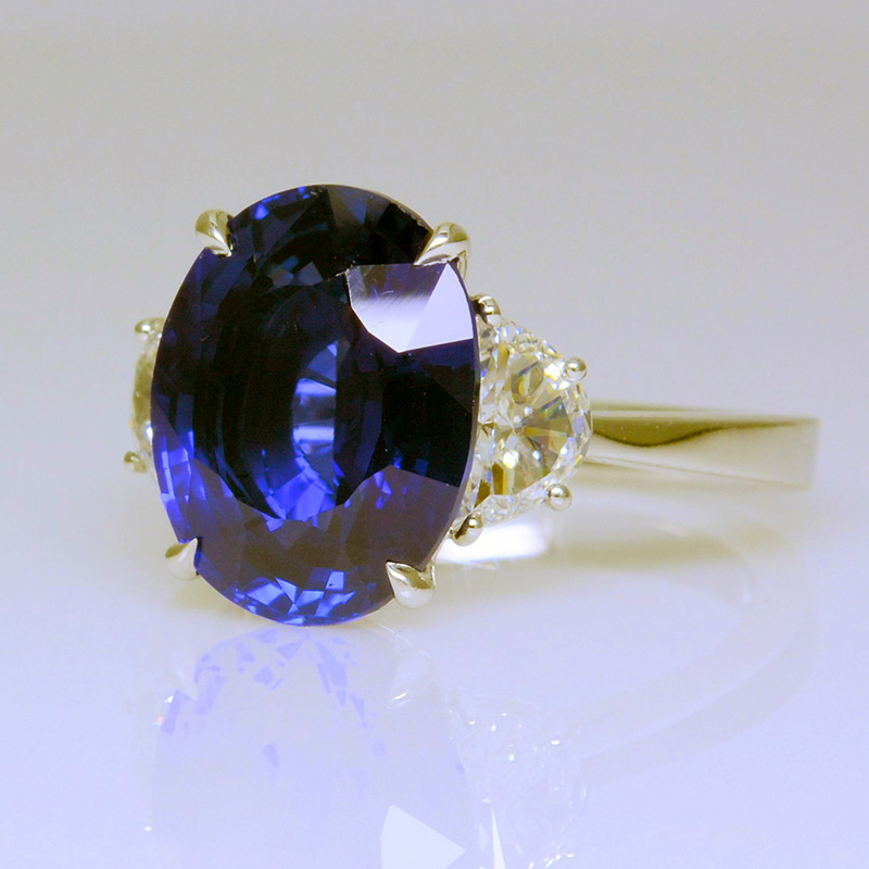 Three stone ring with oval sapphire and half moon diamond side stones