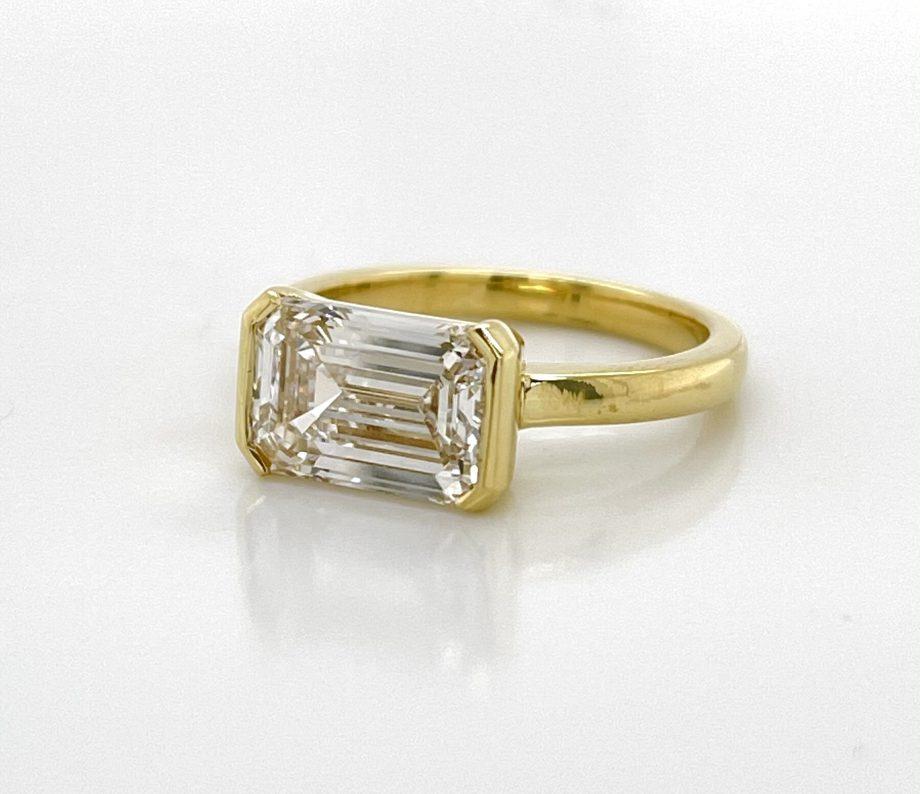 engagement ring featuring an emerald-cut diamond set in an 18k yellow gold half bezel