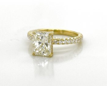 18k yellow gold engagement ring featuring a radiant-cut diamond with a diamond band and gallery