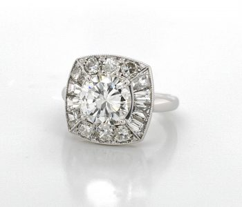 Handmade vintage-inspired engagement ring featuring a round center stone surrounded by baguette and round diamonds
