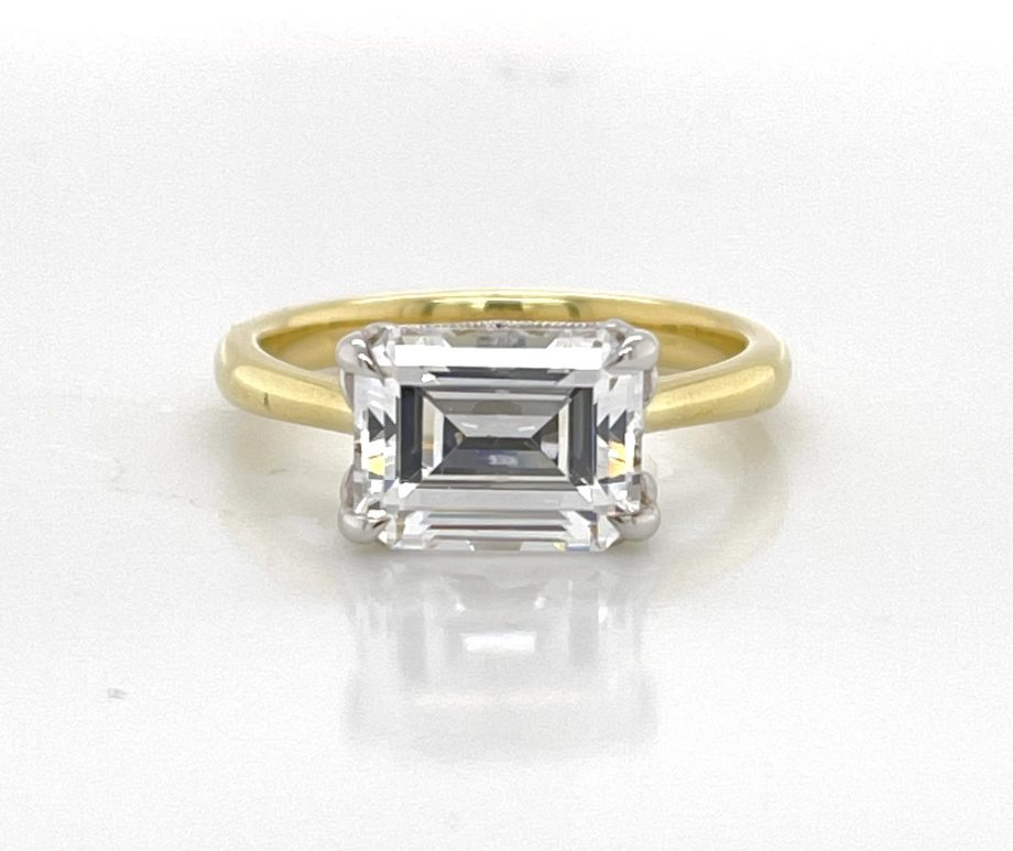 Handmade two-tone engagement ring featuring an east-west emerald-cut diamond in a scalloped gallery
