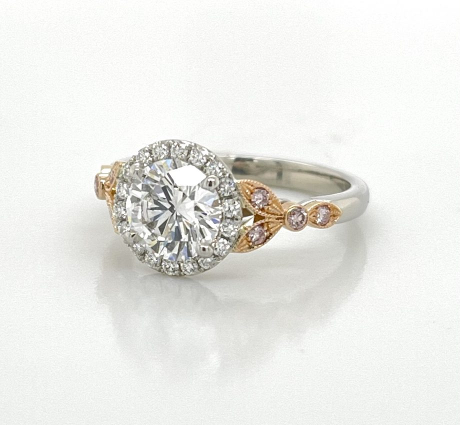 platinum engagement ring featuring a round diamond with a halo and pink diamonds set in rose gold on the ban