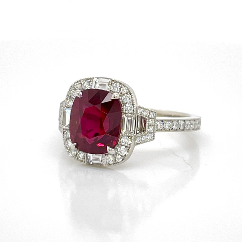 Handcrafted cushion-cut ruby ring featuring diamond buckles and a round and baguette diamond halo