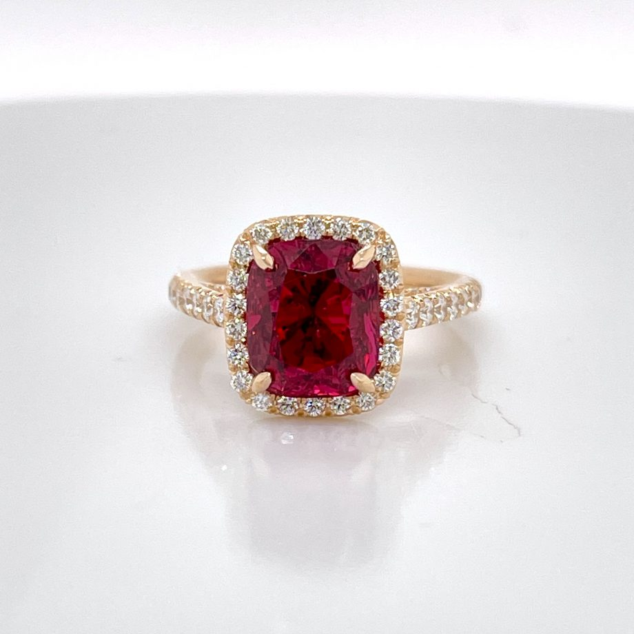 18k rose gold ring featuring a rare red cushion-cut spinel with a diamond halo