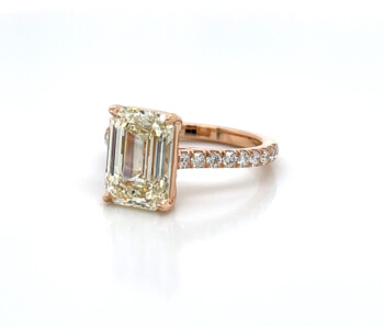 Rose gold engagement ring with emerald-cut diamond on diamond pave band